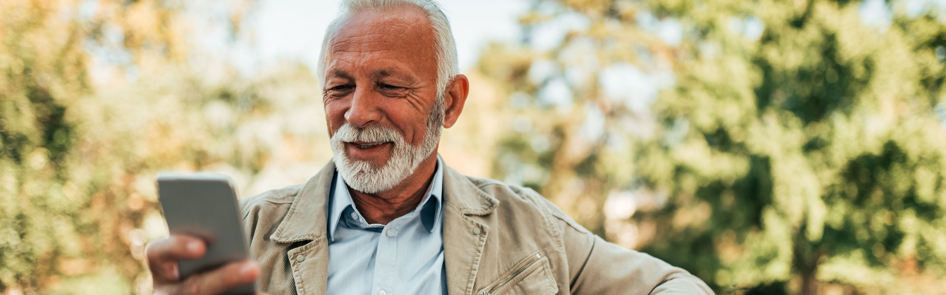A senior man looking at his cell phone