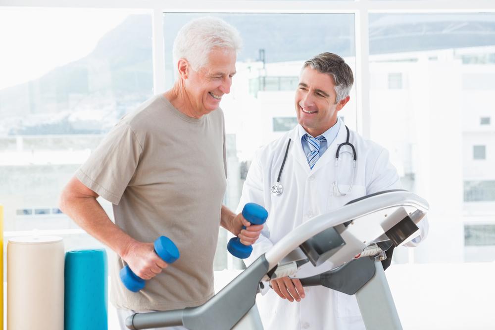 Senior man running on a treadmill next to a doctor