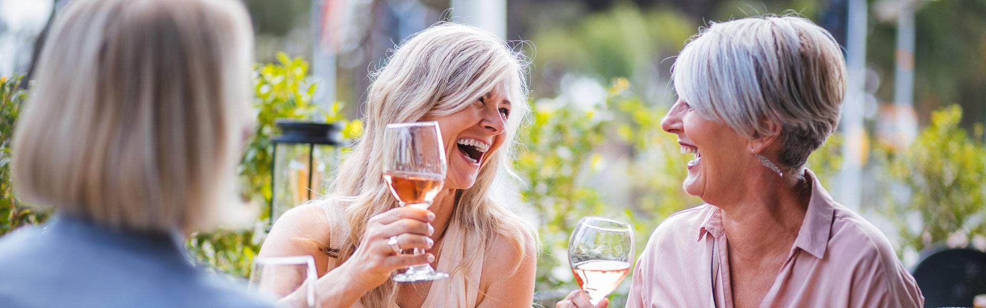 Three older women sitting outside drinking glasses of wine