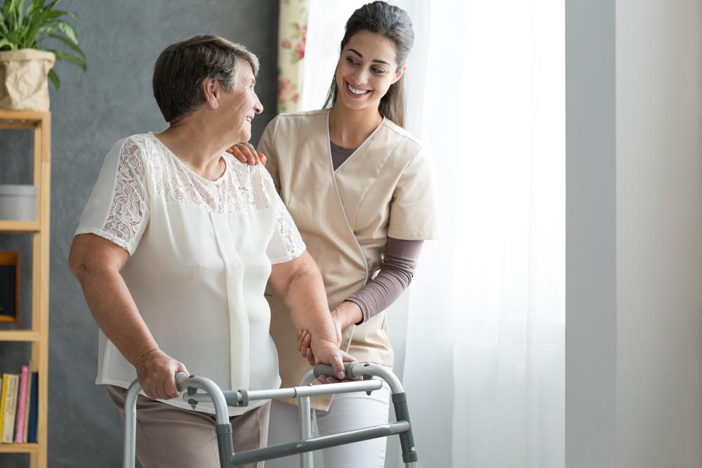Nurse helping senior woman walk with a walker