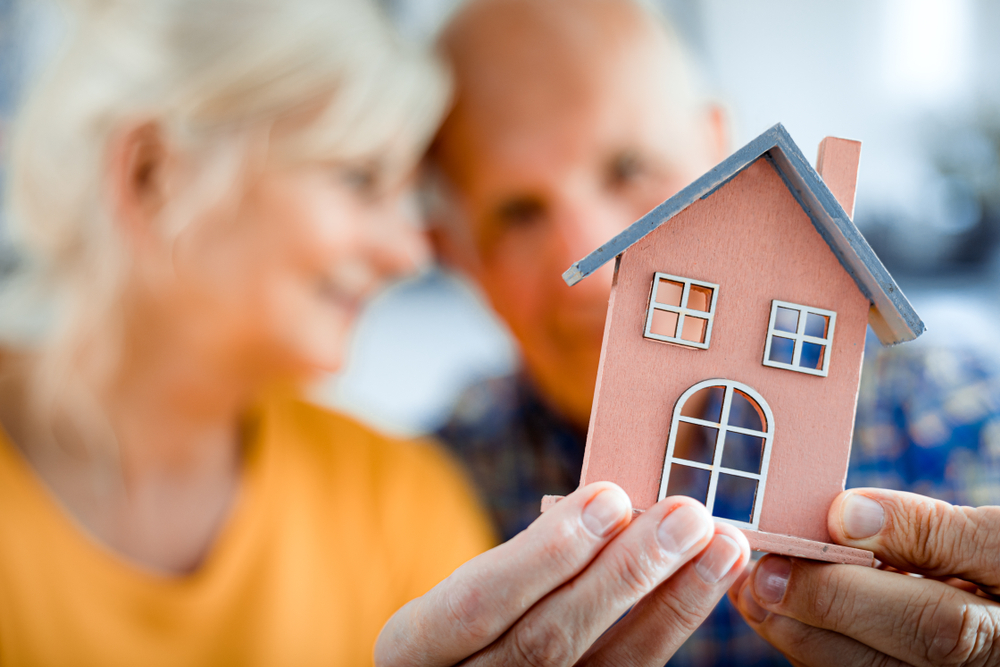 Senior couple holding up tiny house in their hands