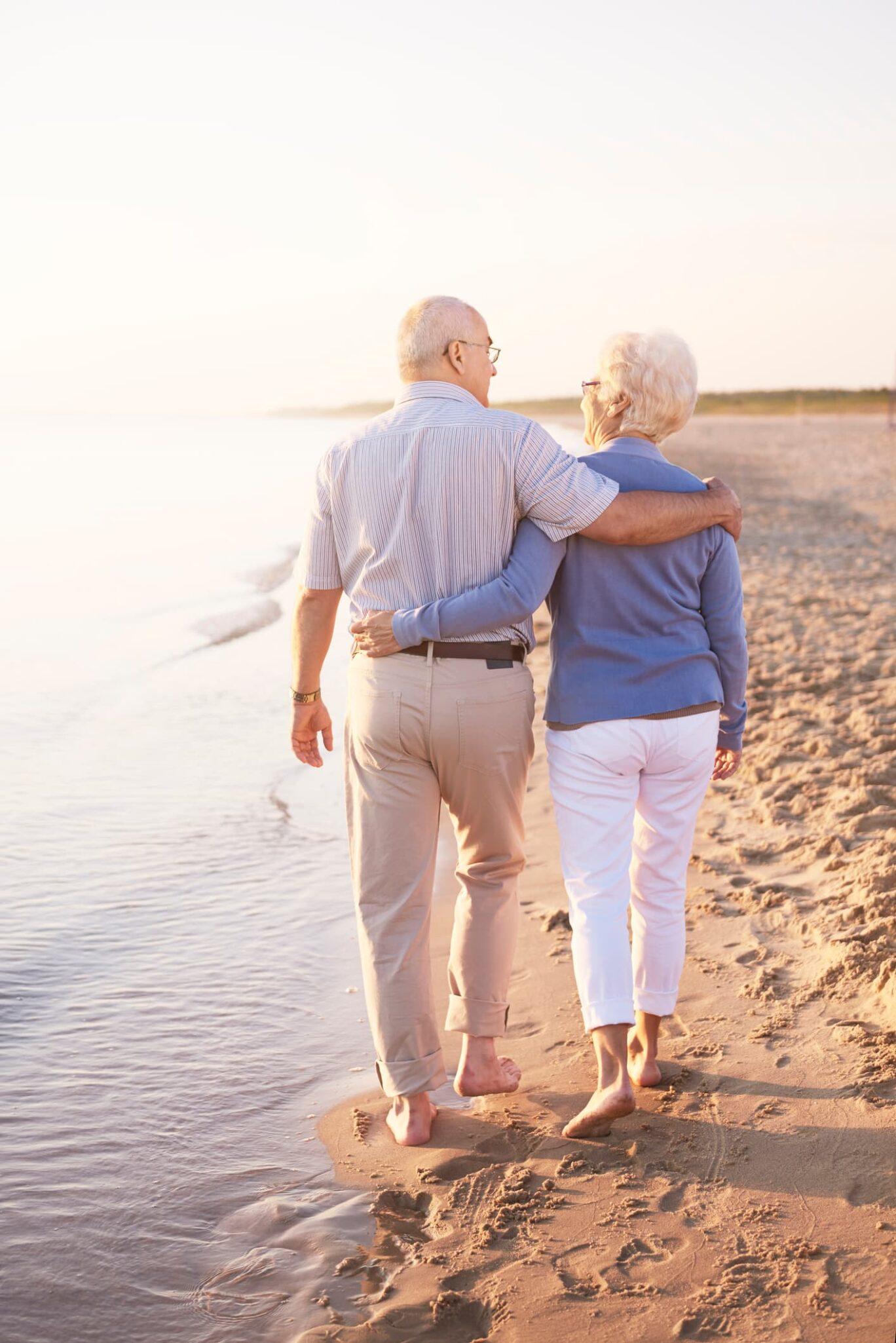 Older couple walking side by side along the beach.
